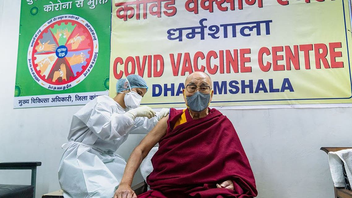 This handout photograph taken on March 6, 2021 and released by the Office of His Holiness the Dalai Lama (OHHDL) shows the exiled Tibetan spiritual leader Dalai Lama getting inoculated with the Covid-19 coronavirus vaccine by a health worker at a vaccination center in Dharamsala.