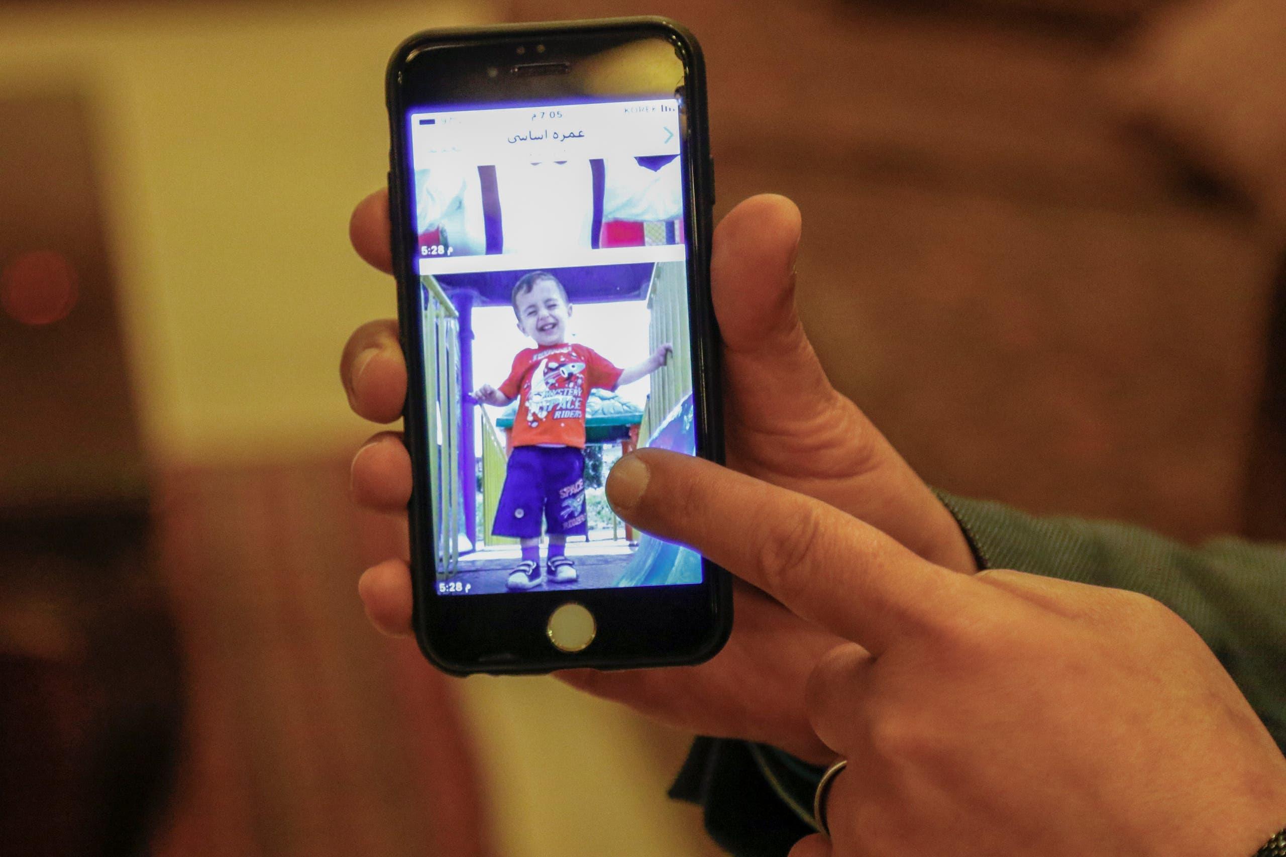 والد آلان كردي يظهر صورة لابنه على هاتفه (أرشيفية)