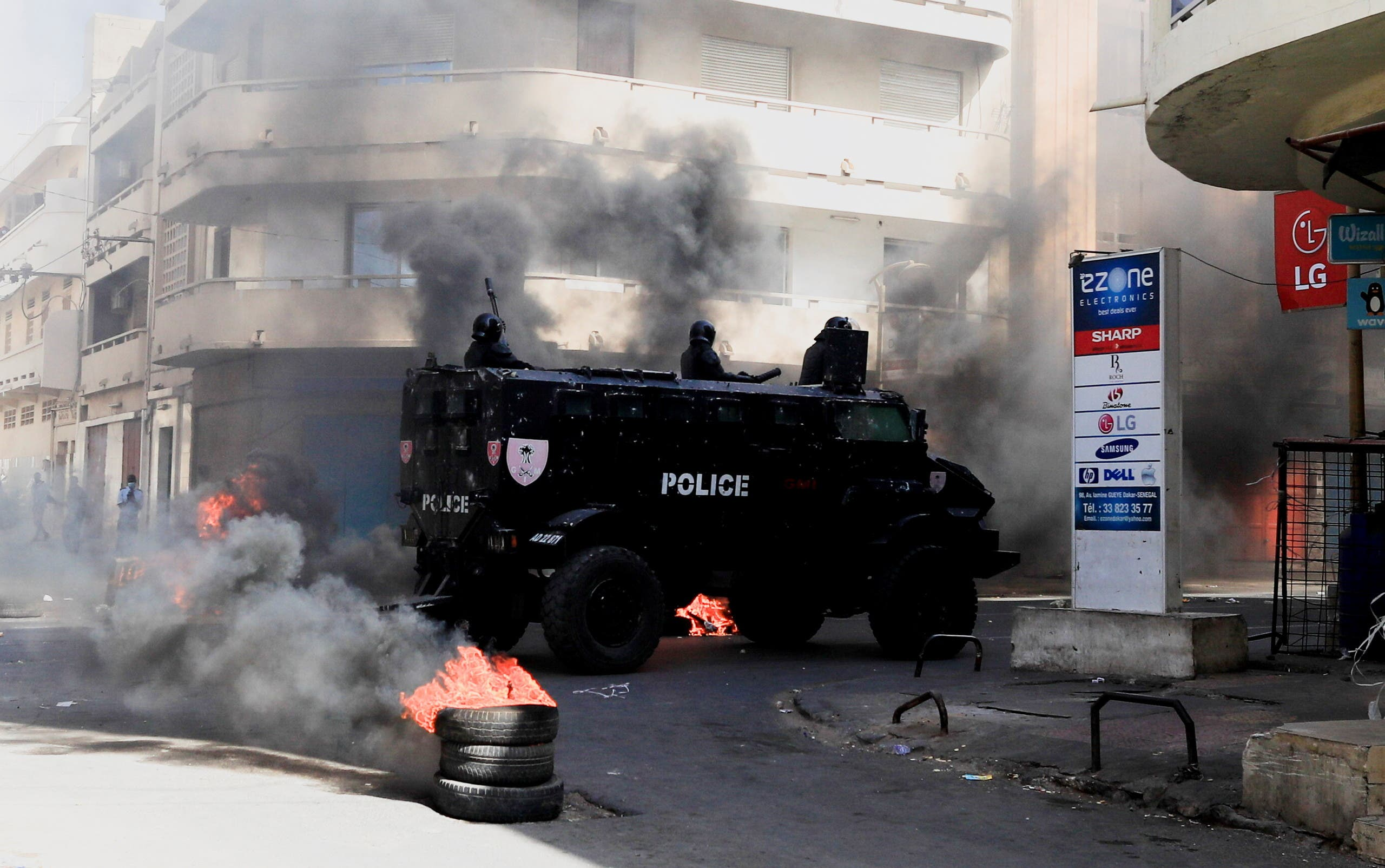 A security forces vehicle drive past burning tyres as supporters of opposition leader Ousmane Sonko, who was arrested following sexual assault accusations, demonstrate in Dakar, Senegal, March 5, 2021. (Reuters)