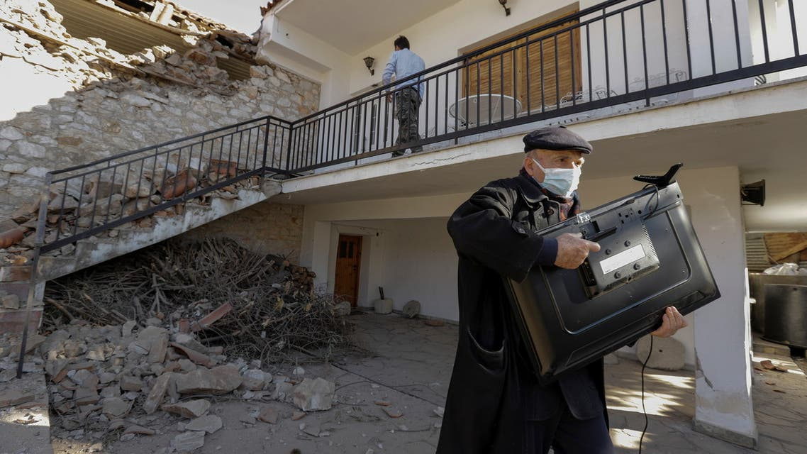 A man carries a TV from his damaged house following an earthquake in the village of Damasi, in central Greece, March 3, 2021. (Reuters)