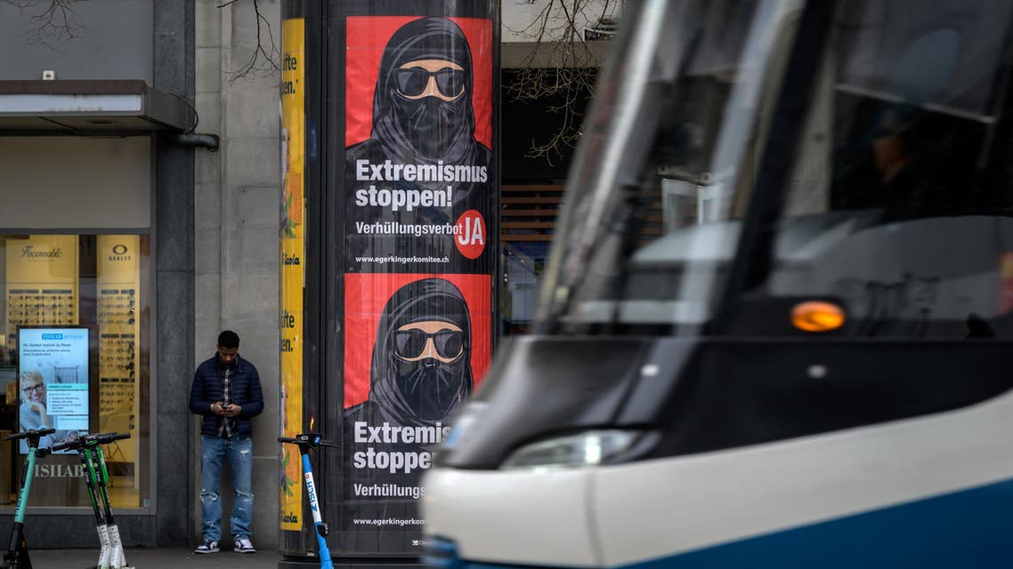 """A tram passes by campaign posters, in favor of the """"burqa ban"""" initiative reading in German: """"Stop extremism!"""" on March 3, 2021 in the streets of Zurich. (AFP)"""