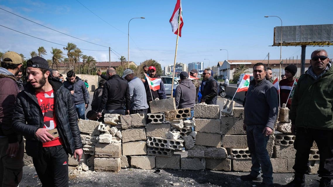Anti-government demonstrators erect a brick wall to block the highway at the southern entrance of Lebanon's northern port city of Tripoli on March 8, 2021 during a protest against the deteriorating value of the local currency and dire economic and social conditions.