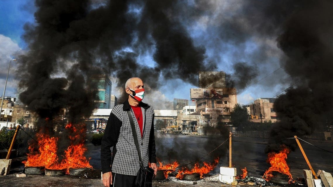 A man clad in mask depicting the Lebanese flag stands next to flaming tires at a make-shift roadblock set-up by anti-government demonstrators in Dora on the northern outskirts of Beirut, March 8, 2021. (Anwar Amro/AFP)