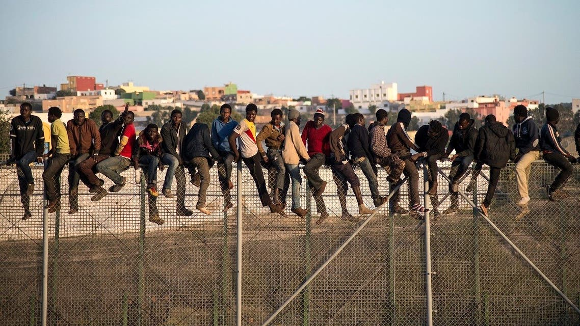 Would-be immigrants stand atop a boarder fence separating Morocco from the north African Spanish enclave of Melilla on October 22, 2014. (AFP)