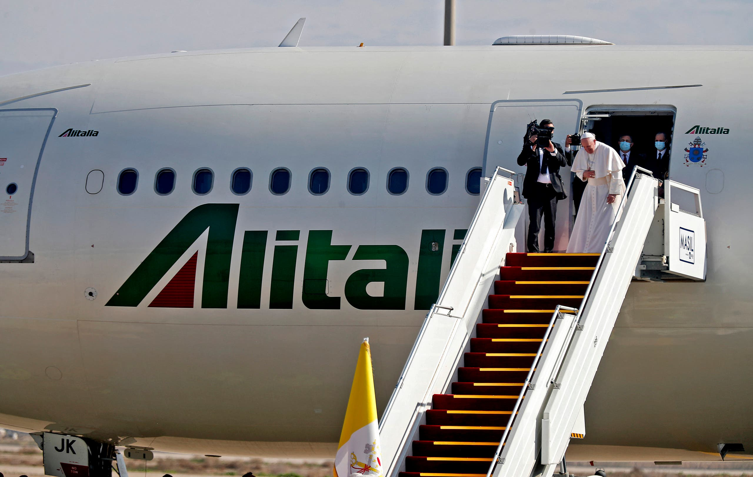 Pope Francis bows in farewell to his hosts before boarding his Alitalia Airbus A330 aircraft as he departs from the Iraqi capital's Baghdad International Airport on March 8, 2021. (AFP)