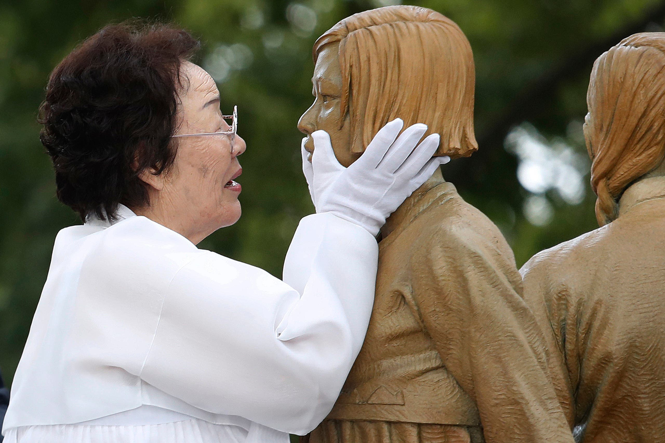 In this Aug. 14, 2019, file photo, Lee Yong-soo, who was forced to serve for the Japanese troops as a sex slave during World War II, touches the face of a statue of a girl symbolizing the issue of wartime comfort women during its unveiling ceremony in Seoul, South Korea. (File photo: AP)