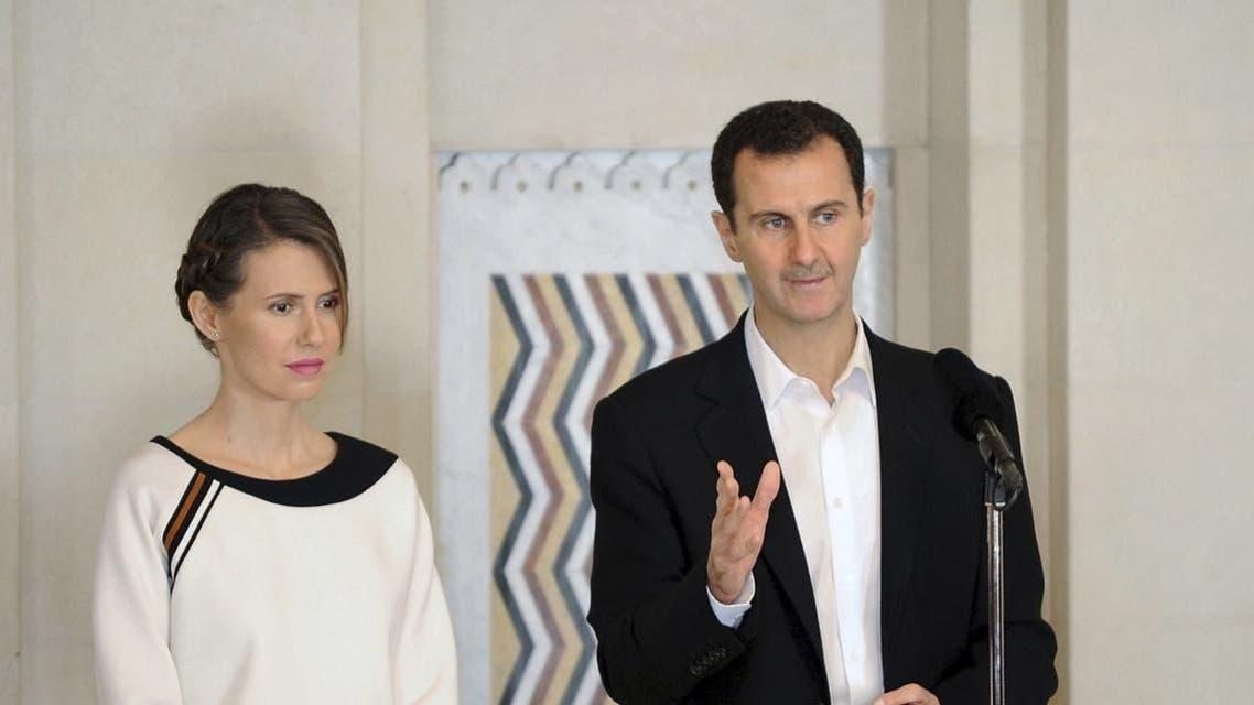Syria's President Bashar al-Assad stands next to his wife Asma
