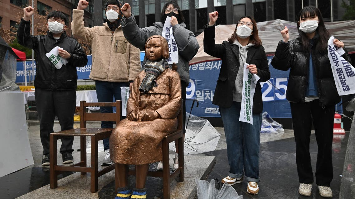 South Korean protesters shout slogans beside a statue (C) of a teenage girl symbolising comfort women, who served as sex slaves for Japanese soldiers during World War II, near the Japanese embassy in Seoul on March 1, 2021, the 102nd anniversary of the Independence Movement Day against the 1910-1945 Japanese colonial rule. (AFP)