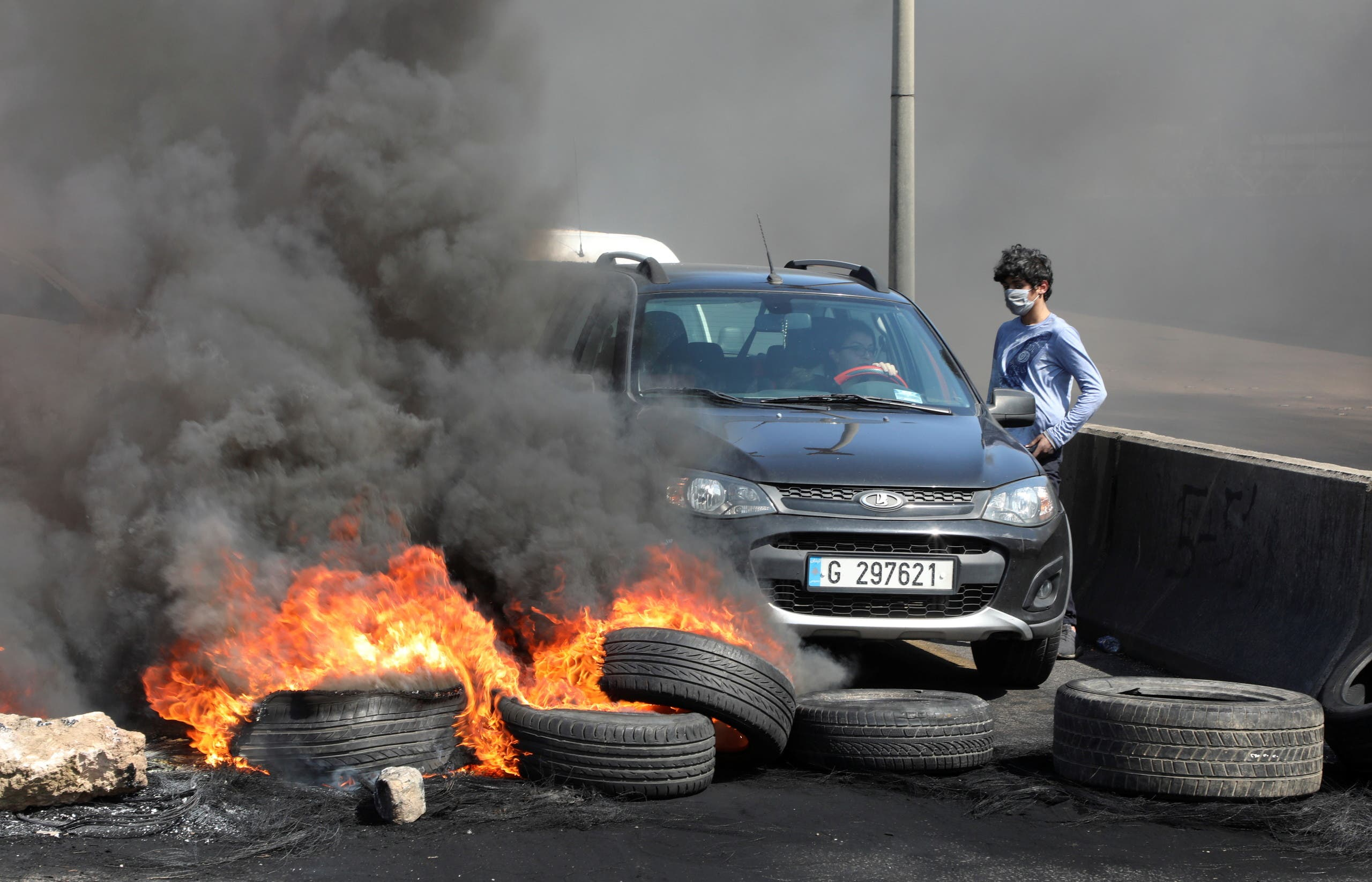 A woman tries to cross a blocked road with burning tires during a protest against the fall in Lebanese pound currency and mounting economic hardships in Khaldeh, Lebanon March 8, 2021. (Reuters)