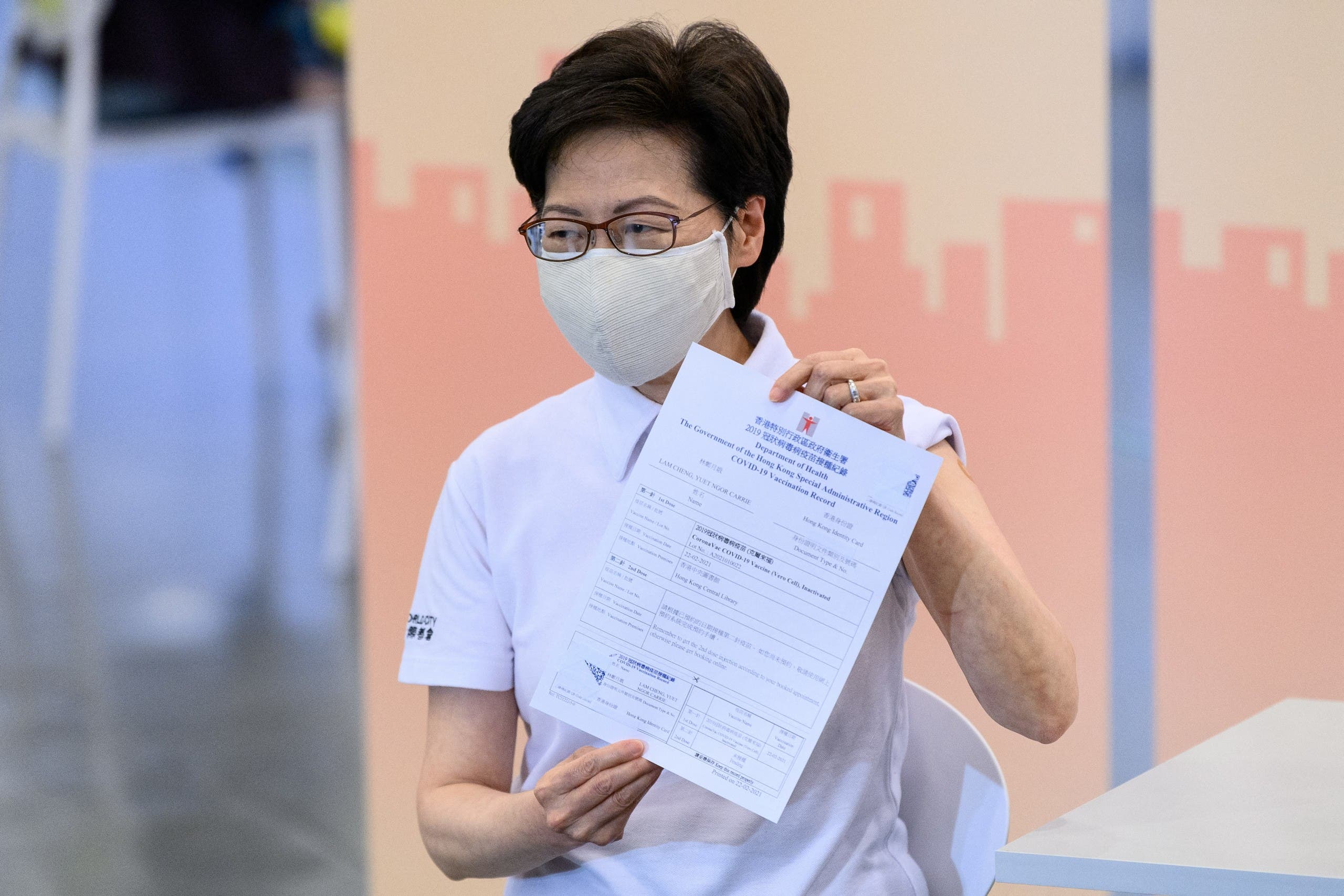 Hong Kong's Chief Executive Carrie Lam holds up a certificate after receiving China's Sinovac COVID-19 coronavirus vaccine at the Community Vaccination Center in Hong Kong on February 22, 2021. (File photo: AFP)