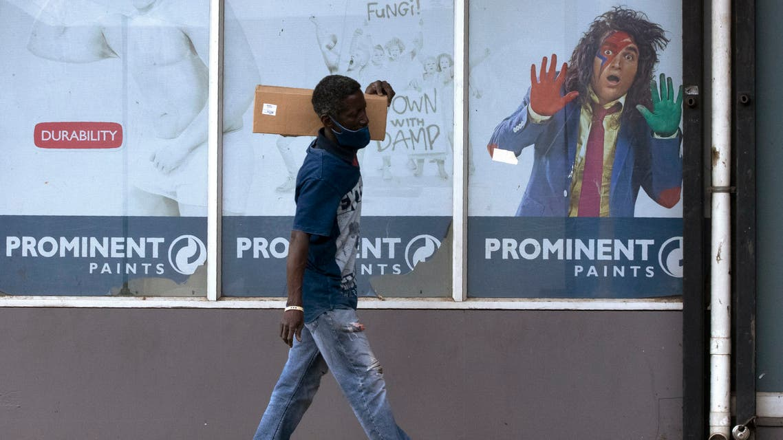 A man wearing a face mask to protect against the spread of the coronavirus walks past a paint advertisement in Alberton, east of Johannesburg, South Africa, Monday, March 1, 2021. (File photo: AP)