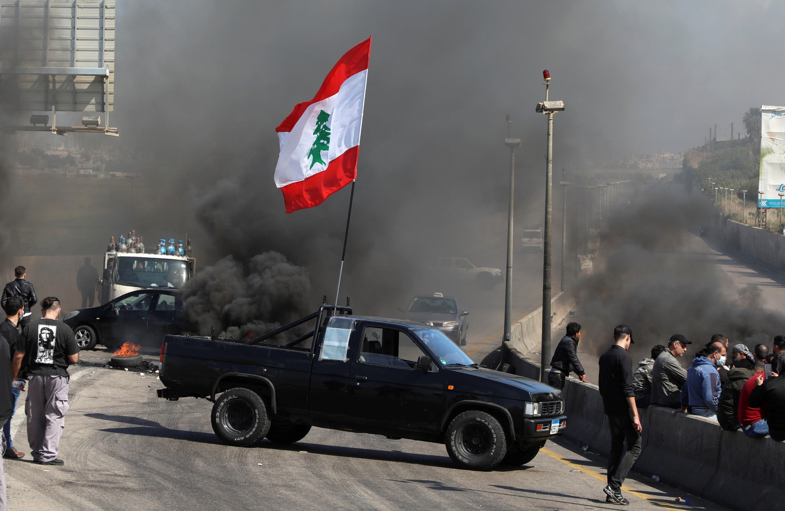 A vehicle blocks a road during a protest against the fall in Lebanese pound currency and mounting economic hardships in Khaldeh, Lebanon March 8, 2021. (Reuters)