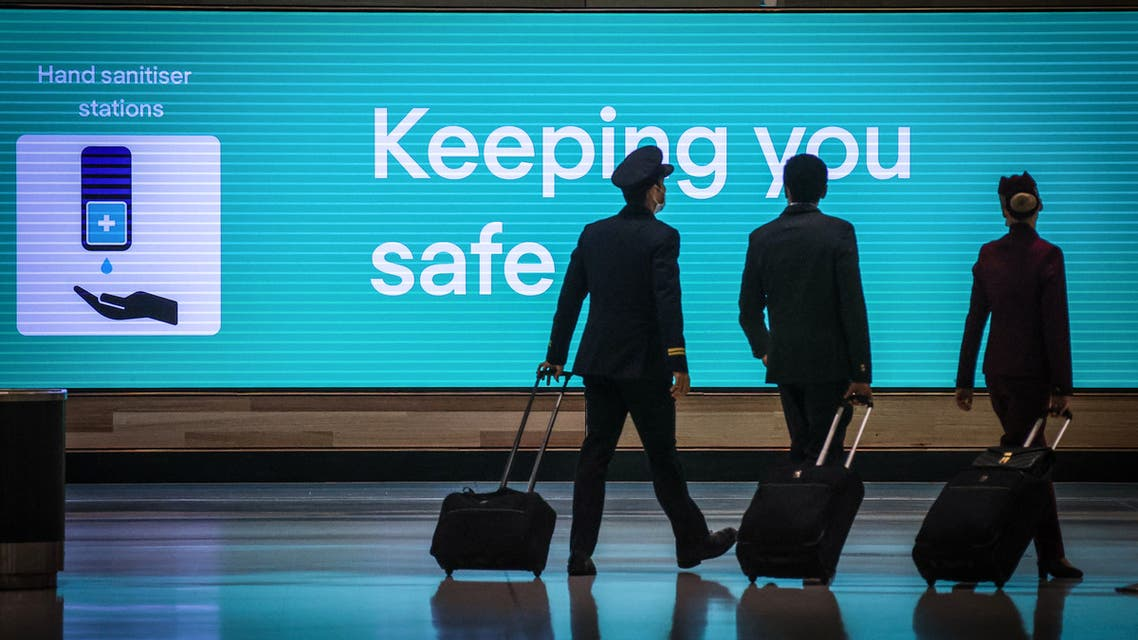 This picture taken on September 29, 2020 shows Qatar Airlines flight crew members walking past an illuminated sign displaying a message relating to the COVID-19 novel coronavirus at the Sydney International Airport in Sydney. (File photo: AFP)