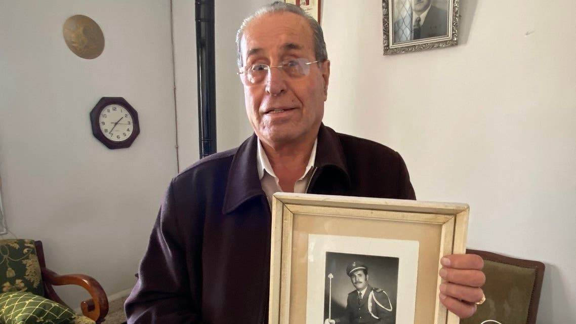 Joseph al-Hajj holds a portrait of himself in his mid 40's in Mtein, Lebanon on March 6, 2021. (Thomson Reuters Foundation/Timour Azhari)