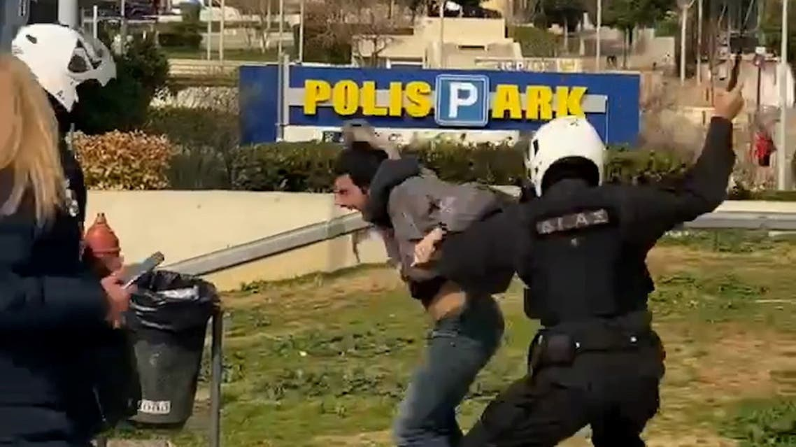 A police officer hits a man as he is being detained in Athens, Greece, March 7, 2021, in this screen grab taken from video. Handout via REUTERS ATTENTION EDITORS THIS IMAGE HAS BEEN SUPPLIED BY A THIRD PARTY.