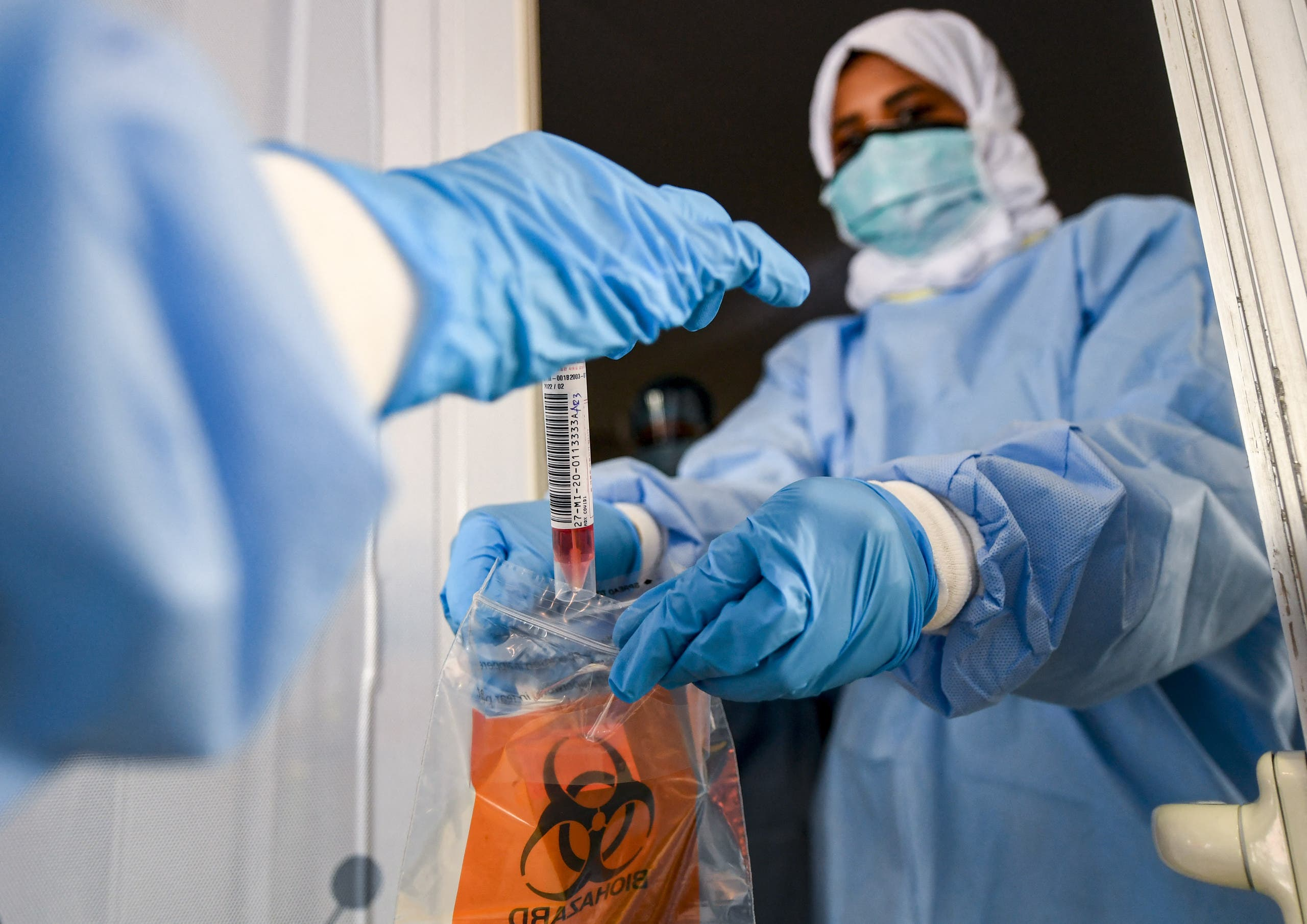 Laboratory workers bag a biological sample at a drive-through COVID-19 coronavirus testing centre in al-Khawaneej district of the gulf emirate of Dubai, UAE. (File photo: AFP)
