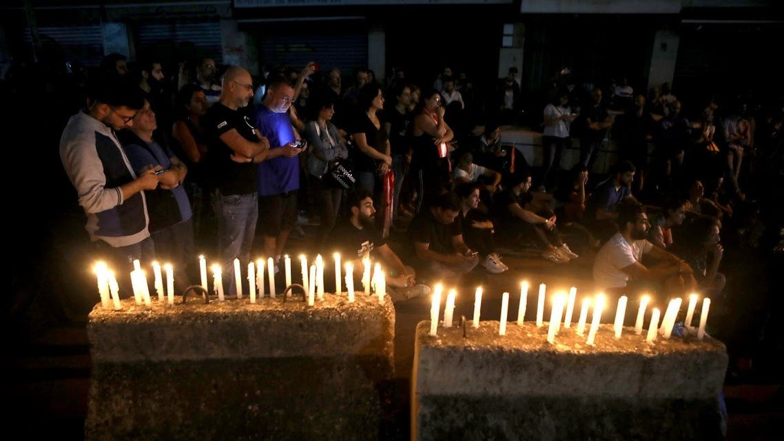 Lebanese anti-government protesters take part in a candle light vigil outside the headquarters of Lebanon Electricity company (EDL) in Beirut. (File photo: AFP)