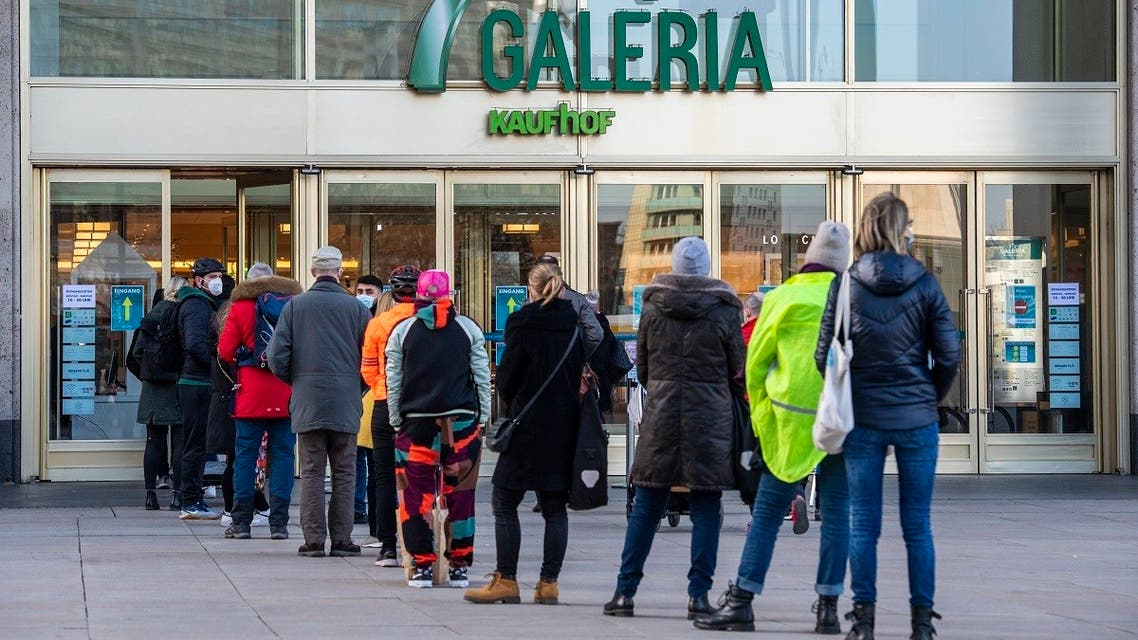 People queue up in front of a department store in Berlin's Alexanderplatz shopping district on March 10, 2021, after some shops were allowed to open following a partial easing of lockdown restrictions, amid a coronavirus pandemic. (AFP)