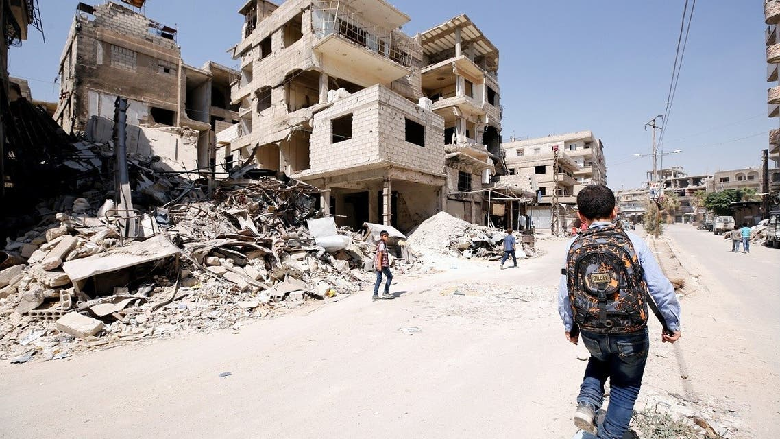 A student walks along a damaged street in the town of Kafr Batna, in eastern Ghouta, Syria. (File Photo: Reuters)