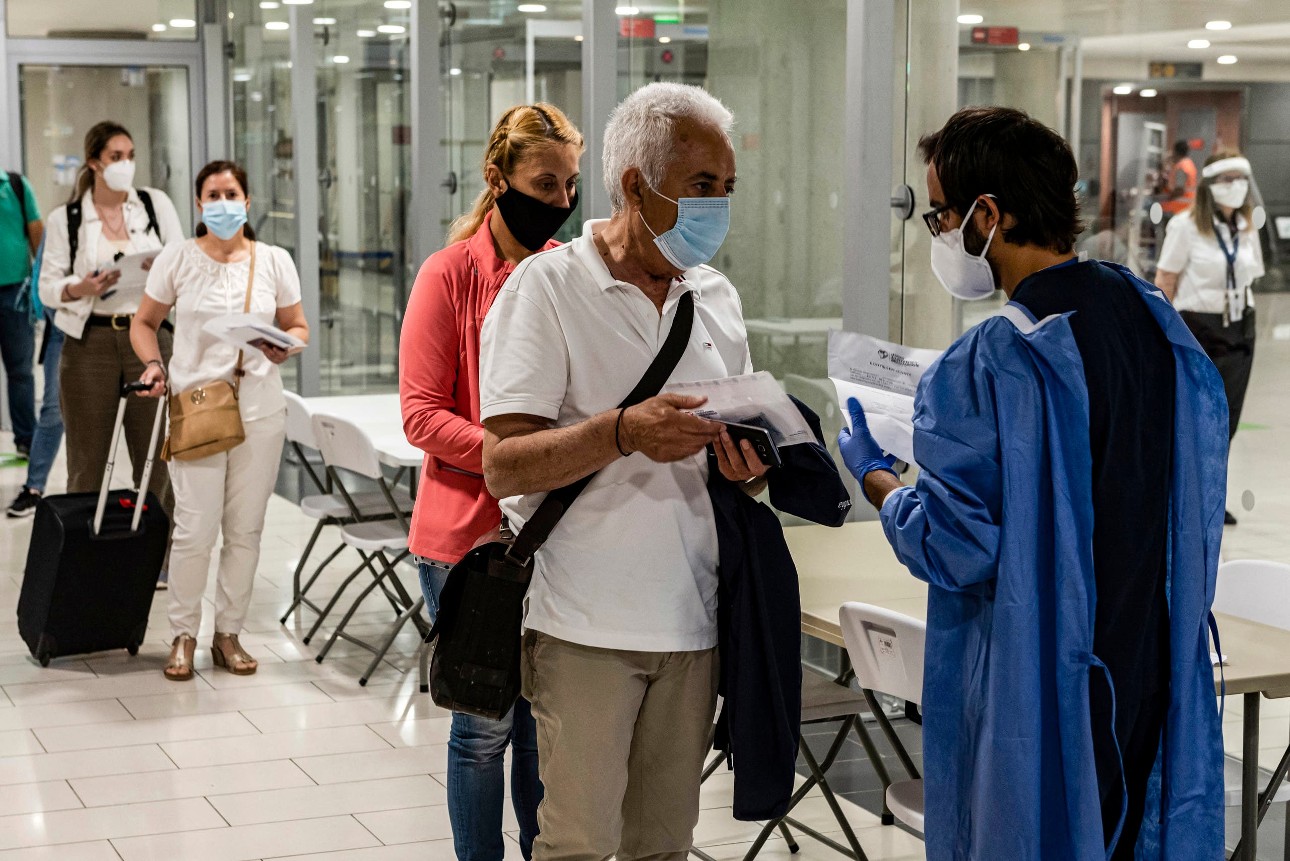 A health worker checks the medical documents of mask-clad travellers arriving at Cyprus' Larnaca International Airport on June 9, 2020, before being screened for COVID-19 coronavirus symptoms on their way to passport control. (File photo: AFP)