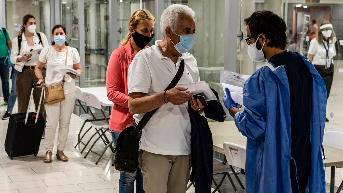 health worker checks the medical documents of mask-clad travellers arriving at Cyprus' Larnaca International Airport on June 9, 2020, before being screened for COVID-19 coronavirus symptoms on their way to passport control. (File photo: AFP)