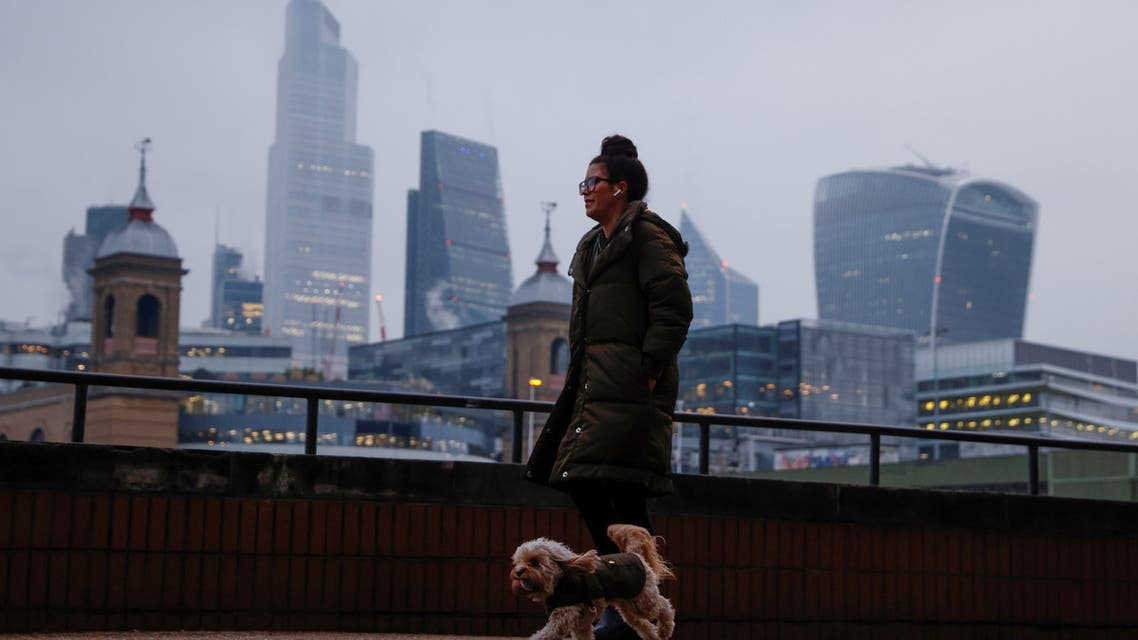 A woman walks her dog along a path next to the River Thames, with the City of London financial district in the background, Britain, January 8, 2021. REUTERS/John Sibley
