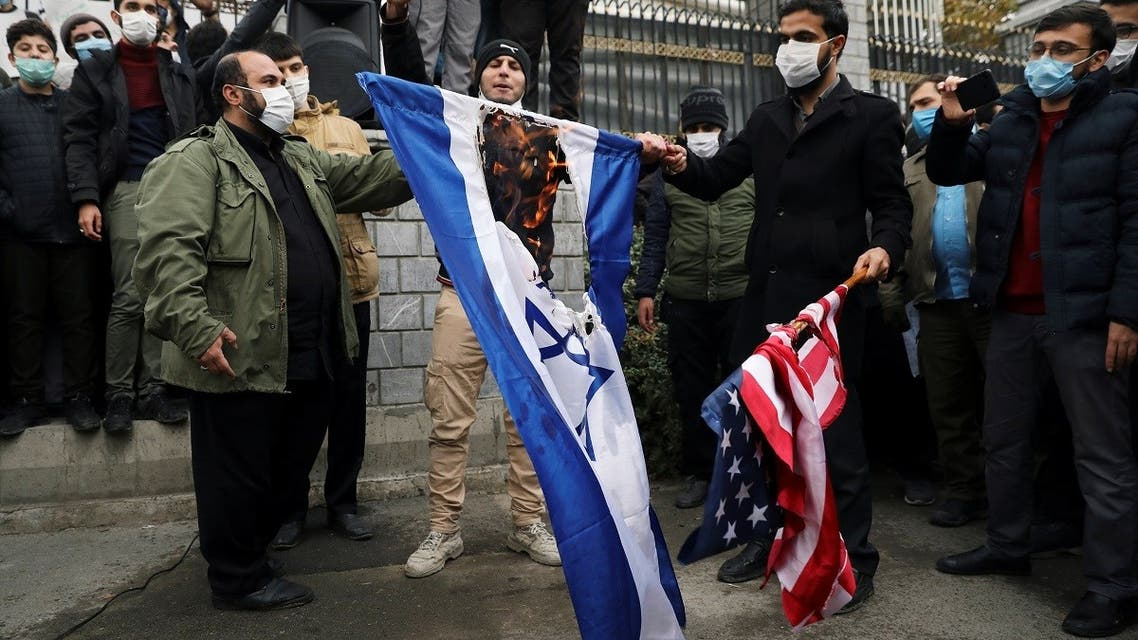 Iranians burn US and Israeli flags during a demonstration against the killing of Mohsen Fakhrizadeh, Iran's top nuclear scientist, in Tehran, Nov. 28, 2020. (Reuters)