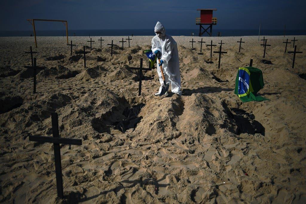 Activists from the Brazilian NGO Rio de Paz (Peace Rio), dig 100 mock graves on Copacabana beach symbolizing deaths from the COVID-19 coronavirus in Rio de Janeiro, Brazil, on June 11, 2020. (AFP)