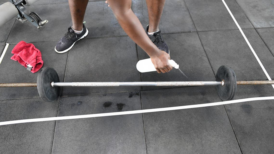 A man cleans a training bar before use at the Fitness 360 gym in Nairobi on August 10, 2020, in line with the safety regulations against COVID-19. (File photo: AFP)