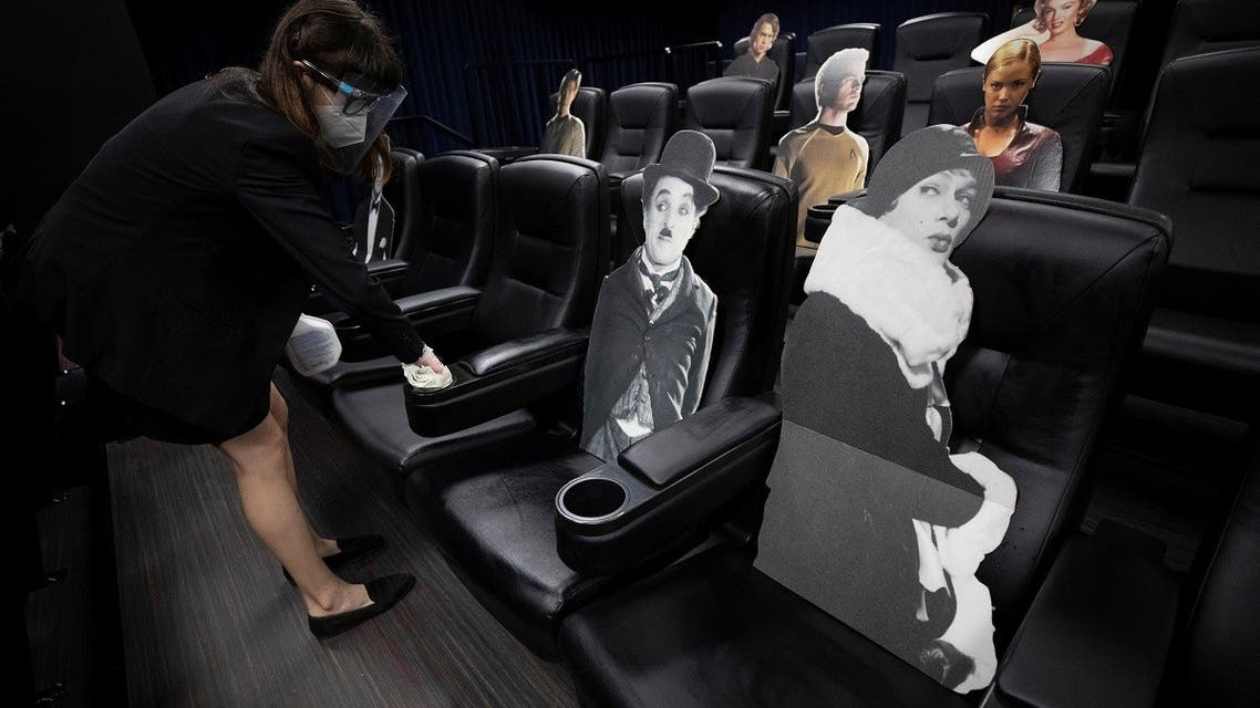 Employee Sophie Castellano sanitizes seats spaced by cardboards of movie characters aimed at social distancing ahead of the reopening of the Arena Cinelounge theatre during the outbreak of the coronavirus disease (COVID-19), in Los Angeles, California. (Reuters)