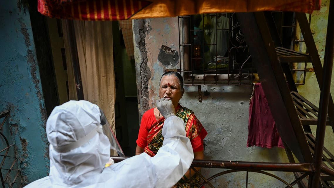 A health worker wearing protective gear takes a swab sample of a resident for a Covid-19 coronavirus test at Dharavi slum in Mumbai on March 11, 2021. (AFP)