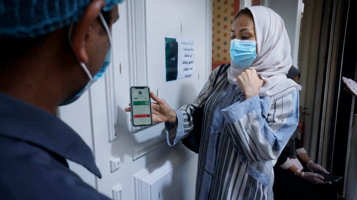 Saudi Hala Abdullah shows her page on the Tawakkalna app, which was launched by Saudi authorities last year to help track coronavirus infections, as she enters a shop in Jiddah, Saudi Arabia, Friday, Feb. 5, 2021. (File photo: AP)