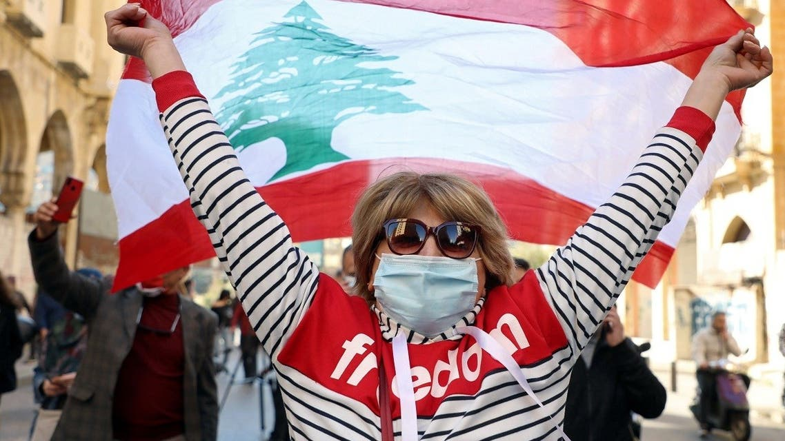 A demonstrator holds up a national flag during a protest in Beirut, Lebanon March 6, 2021. (Reuters)