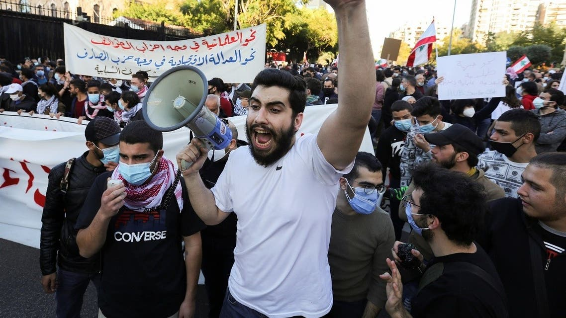 A demonstrator gestures while carrying a megaphone during a protest against the fall in Lebanese pound currency and mounting economic hardships, in Beirut, Lebanon March 12, 2021. (Reuters)