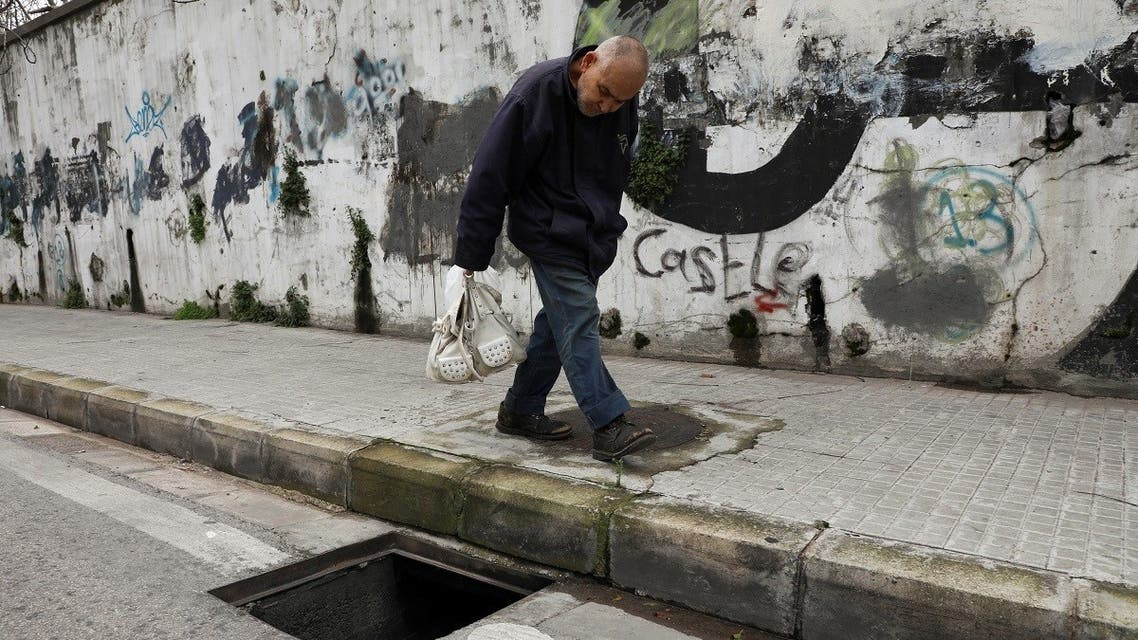 A man walks past a manhole with a missing cover in Beirut, Lebanon March 4, 2021. (Reuters)