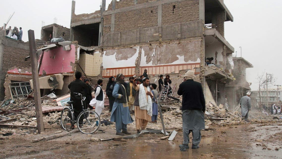 Residents stand amid the debris of a damaged house after a car bomb blast in Herat on March 13, 2021.