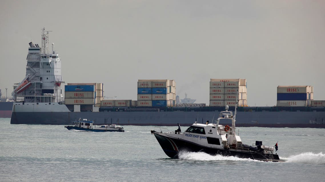 A police coast guard vessel patrols past container ship Valili carrying Islamic Republic of Iran Shipping Lines (IRISL) cargo in the waters of Singapore Strait off Sentosa island February 6, 2012. (Reuters)