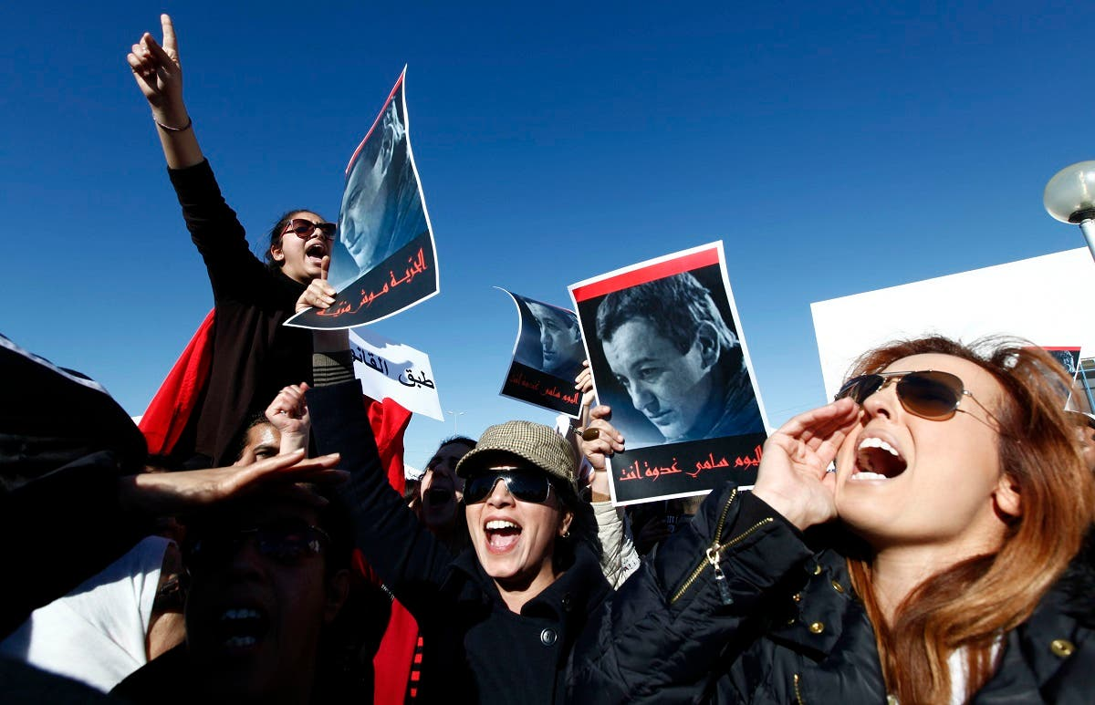 Tunisian protesters hold posters depicting Sami Fehri, TV producer and director of Ettounsiya Television, during a demonstration outside Mornaguia jail calling for the liberation of Fehri, in Tunis December 24, 2012. (Reuters)