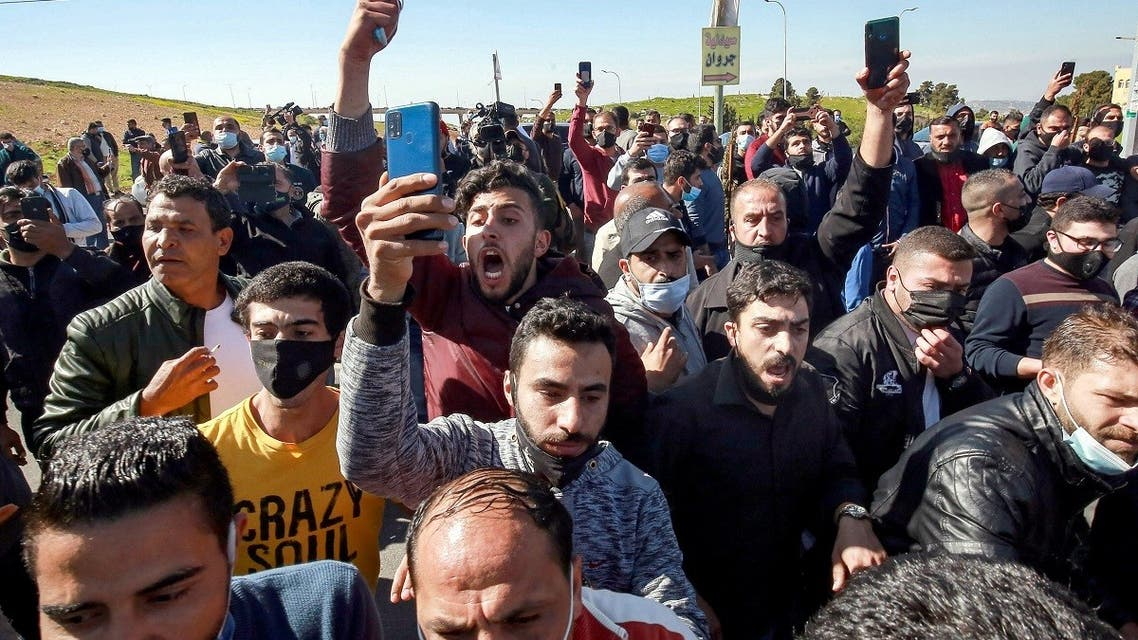People protest outside al-Hussein New Salt Hospital in the town of Salt, northwest of Jordan's capital, on March 13, 2021. (AFP)