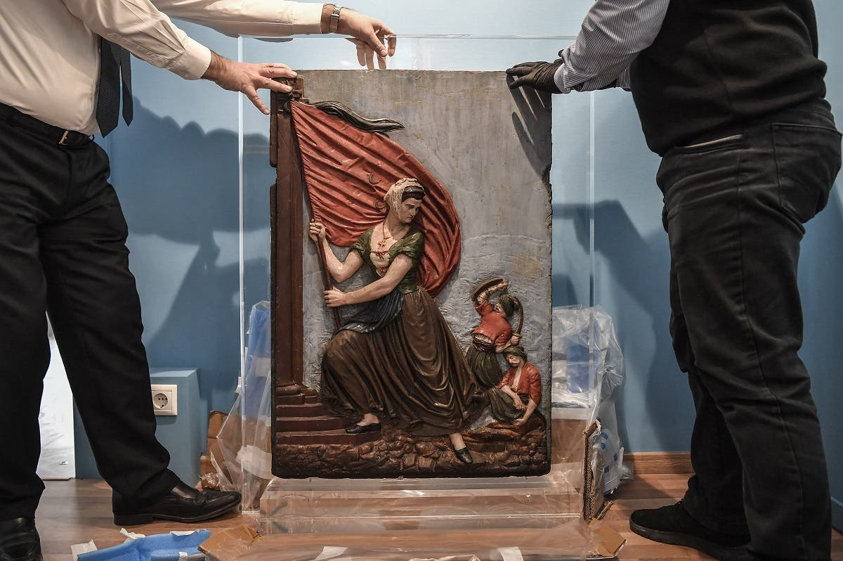 Museum employees unwrap an artwork depicting Greek revolution heroine, Laskarina Bouboulina in the new museum dedicated to the Philhellene foreign volunteers who fought and died for Greece on March 12, 2021. (Louisa Gouliamaki/AFP)