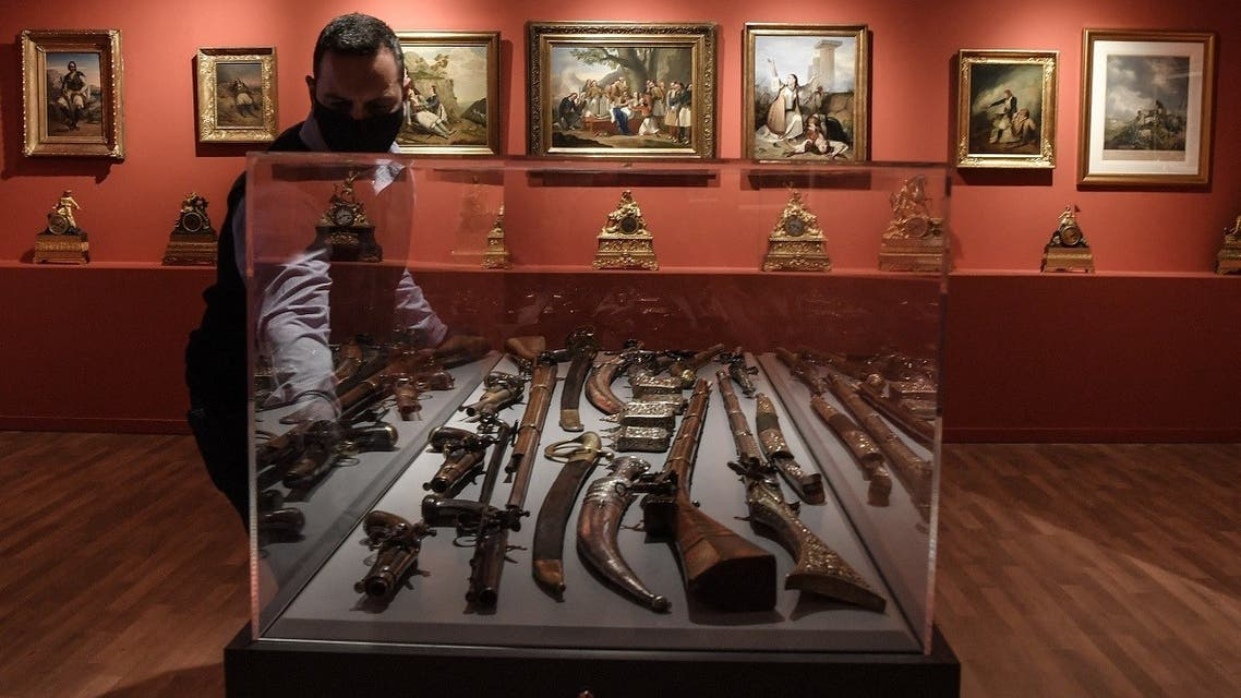 A museum employee closes a case displaying weapons in the new museum dedicated to the Philhellene foreign volunteers who fought and died for Greece on March 12, 2021. (Louisa Gouliamaki/AFP)