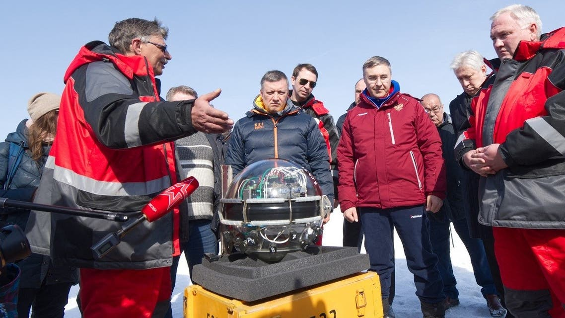 This handout picture released on March 13, 2021 shows scientists and officials watching the underwater neutrino telescope being immerged into the water of the Baikal lake. (Bair Shaibonov/Russian Institute for Nuclear Research/AFP)