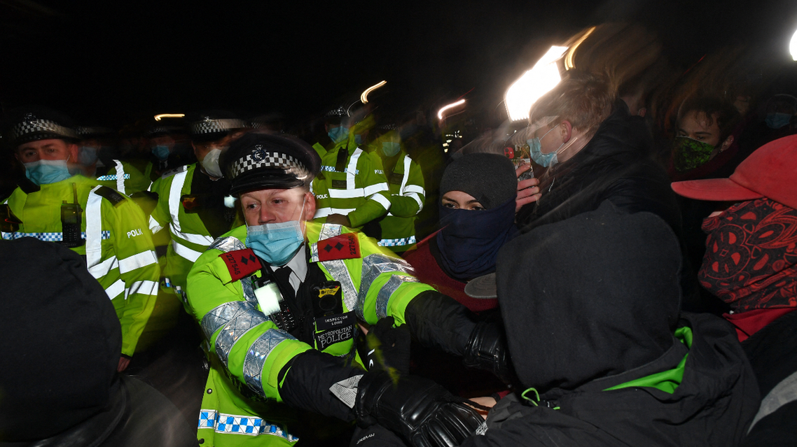 Police scuffle with people gathering at the band-stand where a planned vigil in honor of murder victim Sarah Everard, which was officially cancelled due to COVID-19 restrictions, was to take place on Clapham Common, south London on March 13, 2021. (AFP)