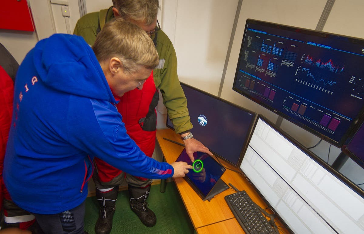 This handout picture released on March 13, 2021 shows scientists and officials checking a screen during an operation to immerge the underwater neutrino telescope into the water of the Baikal lake. (Bair Shaibonov/Russian Institute for Nuclear Research/AFP)