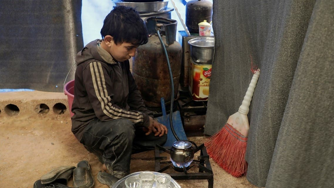 Mohammed Abu Rdan prepares tea inside a tent, at an internally displaced Syrian camp, in northern Aleppo, Syria March 11, 2021. (Reuters/Mahmoud Hassano)