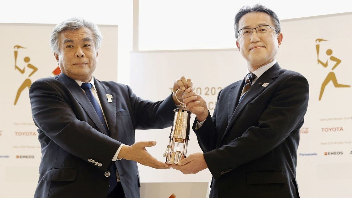 Makoto Noji, head of bureau of culture and sports for Fukushima government, holds the Olympic Flame in lantern with Tokyo 2020 COO Yukihiko Nunomura during an official ceremony at the J-Village National Training Center, in Naraha Town, Fukushima Prefecture, Japan, on April 1, 2020. (Reuters)