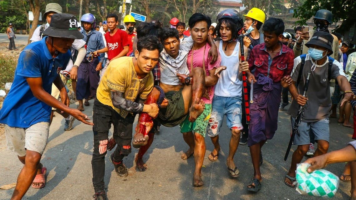 A resident, who was injured during a crackdown by security forces on demonstrations by protesters against the military coup, is carried to safety in Yangon's Hlaing Tharyar township on March 14, 2021. (STR/AFP)