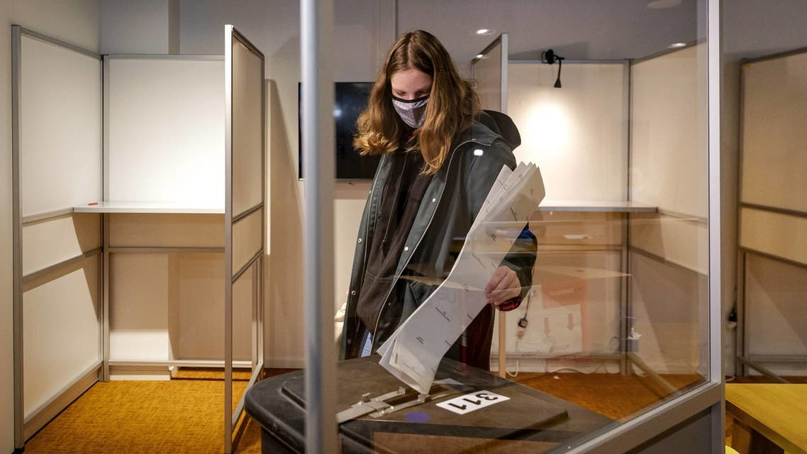 A voter casts her ballot to vote in the House of Representatives elections at a polling station in Utrecht, on March 15, 2021. (AFP)