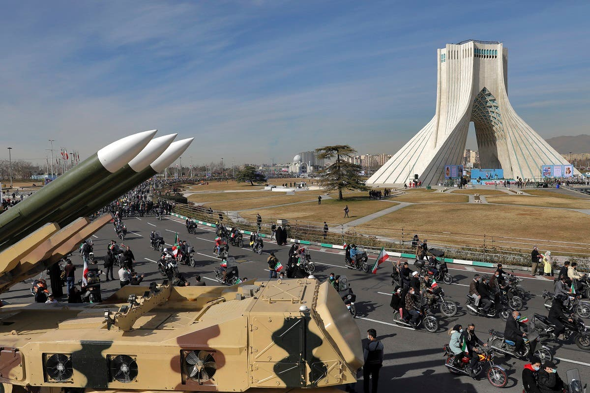 Iranians drive past missiles on motorcycles during a rally marking the 42nd anniversary of the Islamic Revolution, at Azadi (Freedom) Square in Tehran, Iran, on February 10, 2021. (AP)