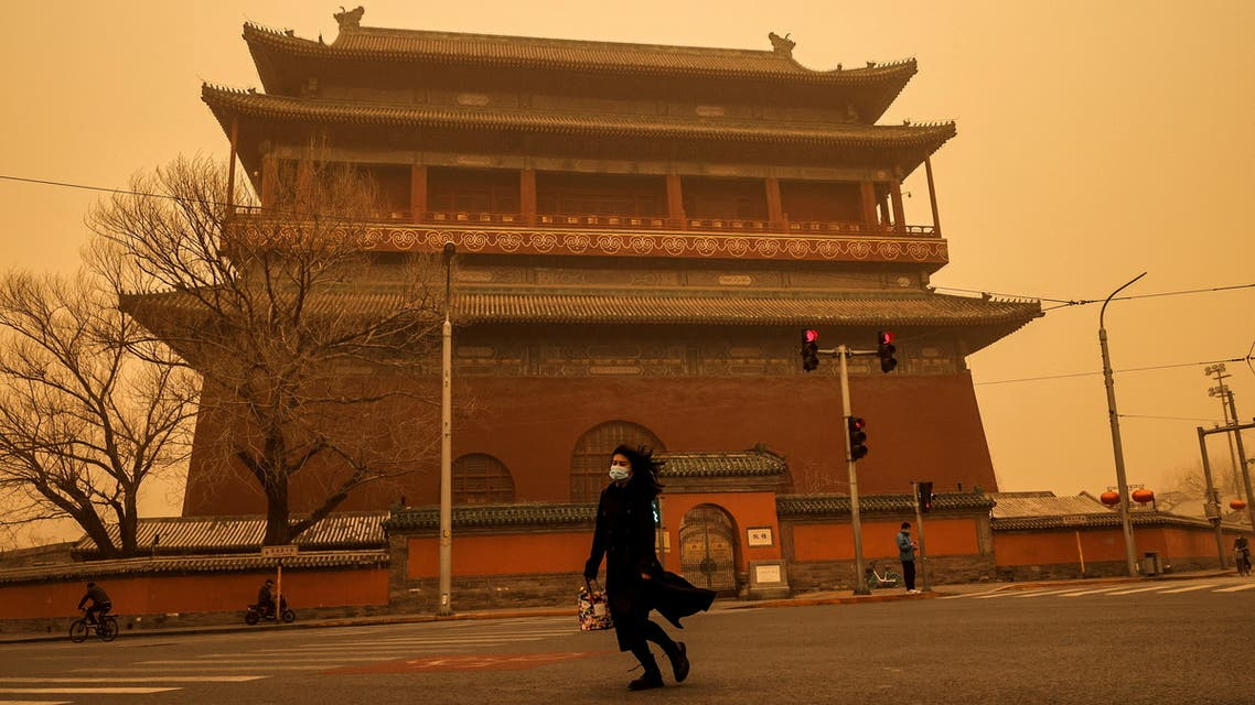 A woman walks past Drum Tower during morning rush hour as Beijing, China, is hit by a sandstorm, March 15, 2021. (Reuters)